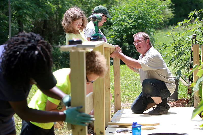 Volunteers work together to build the rail for a wheelchair ramp to make a home more accessible. (Photo courtesy of Jared Putnam)