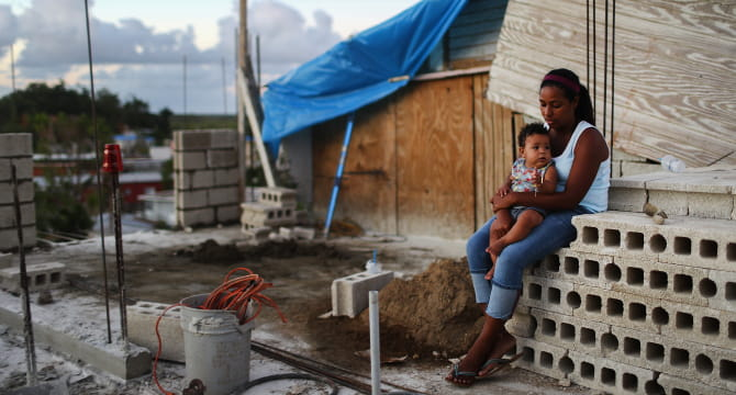 A mother holds her 9-month-old baby three months after Hurricane Maria destroyed their home in Puerto Rico