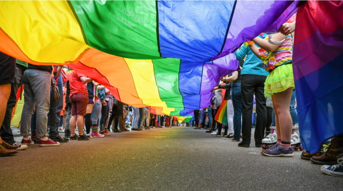 Group of people walking with rainbow parachute