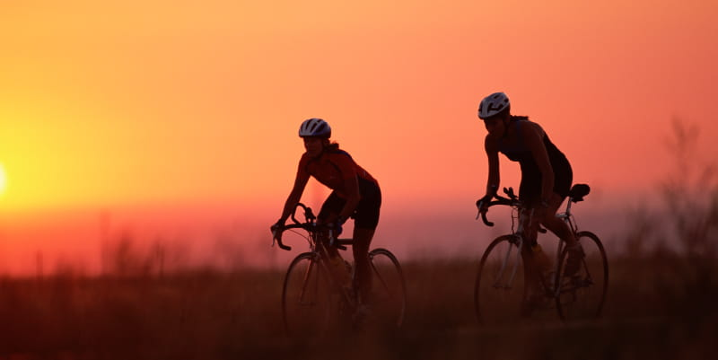 Two bicyclists riding at sunset.