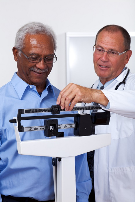 Man being weighed by doctor 467x700