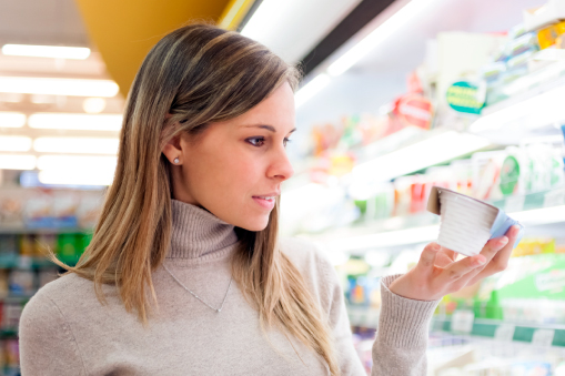 Woman at grocery store looking at yogurt