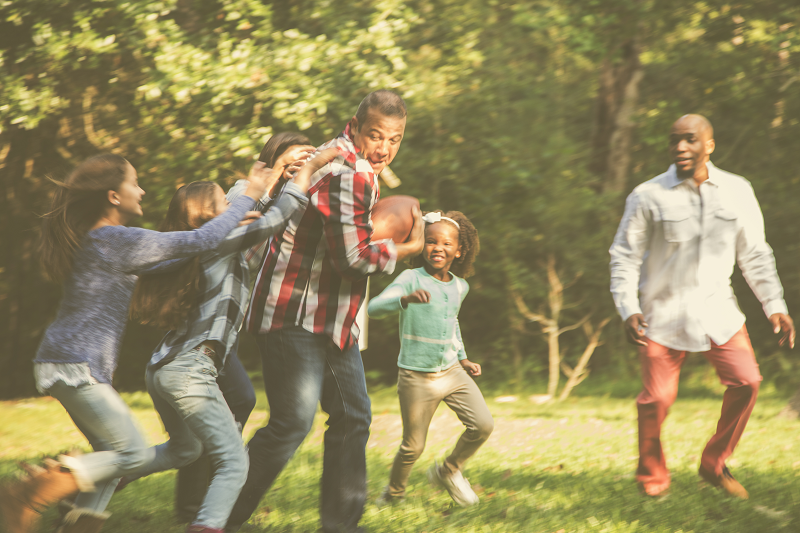 multi-ethnic family playing football outside