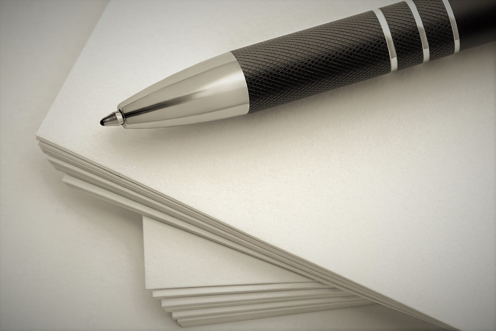 pen laying on stack of papers