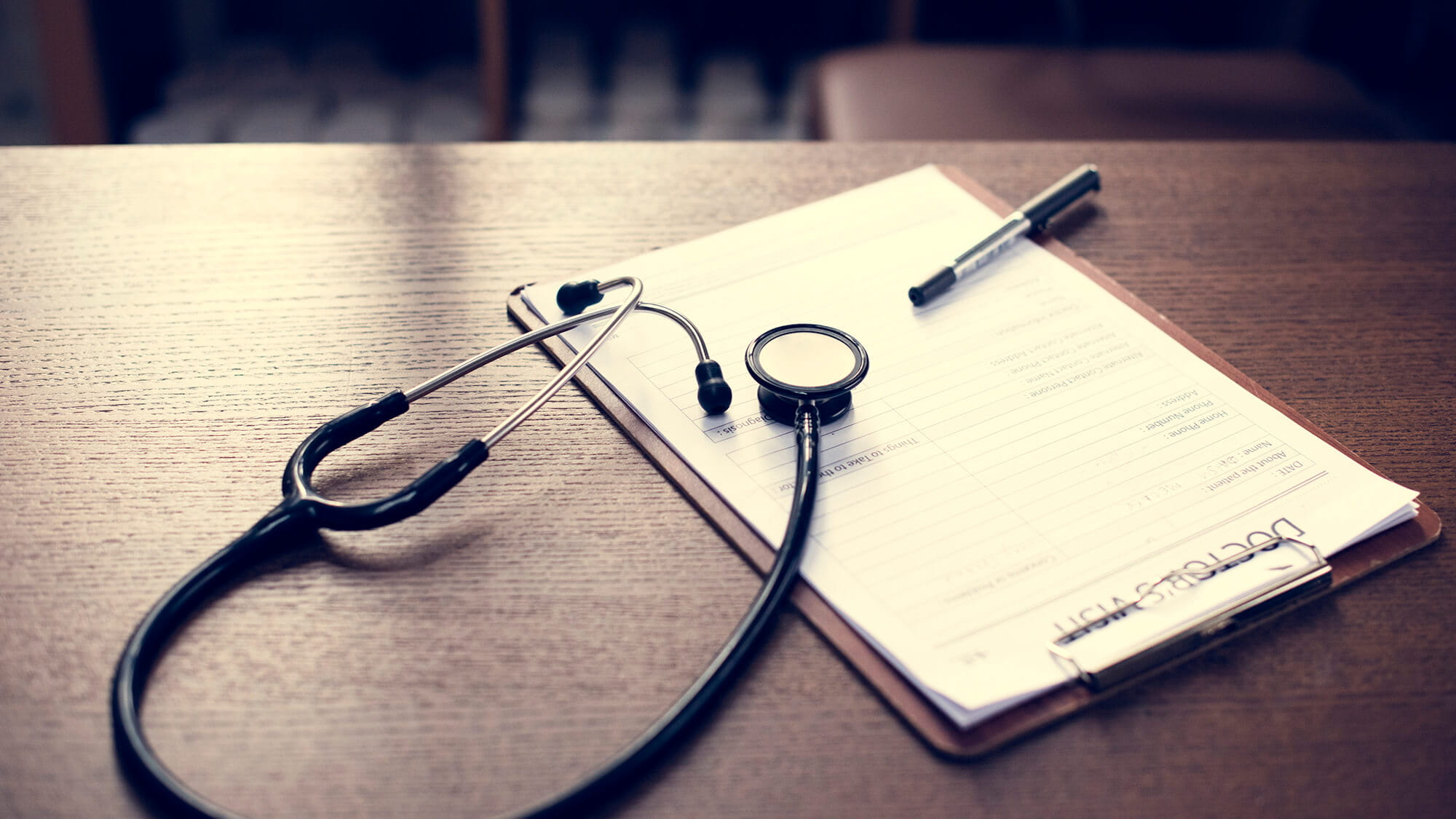 checkup form and stethoscope laying on desk