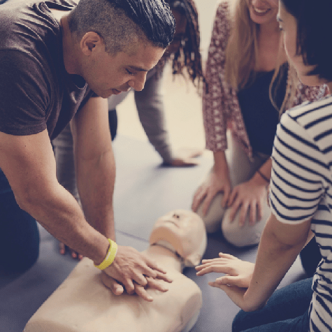 man performing CPR on CPR manikin