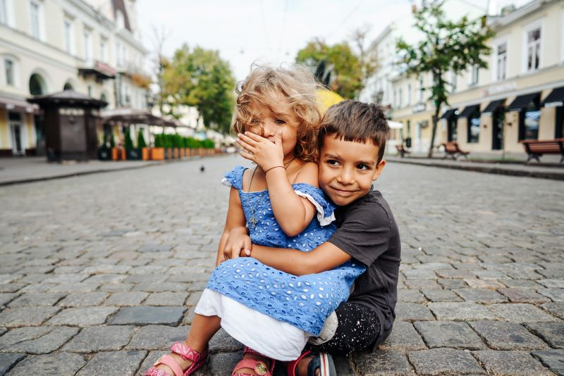 Young children sitting in a street